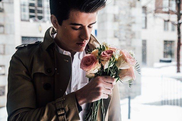 Mies kukkakimpun kanssa