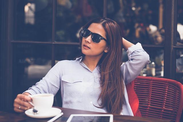 Nainen istuu kahvilla